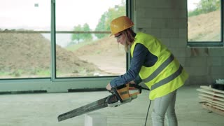 Female worker on the building site. Beautiful young woman cutting building blocks. House construction