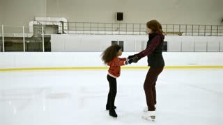 Figure skating coach holding hands with little African girl while teaching her how to skate on one leg at indoor ice rink