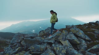 Fit young woman in a stylish look with a backpack wanders in the fog mountains. Hiking, extreme, active lifestyle. Indie look, hipster. Slow motion, camera stabilizer shot, female portrait
