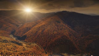 Flight over dramatic autumn sunset landscape. Small mountain village in canyon surrounded meadows, orange hills, pine tree forests. Carpathians, Ukraine, Europe. Vintage retro dark toning filter. 4K