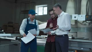 Foreman standing and talking two workers with blueprints in furniture factory room