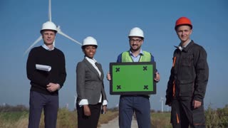 Four engineers standing against wind turbines and holding creative copyspace with green screen in hands
