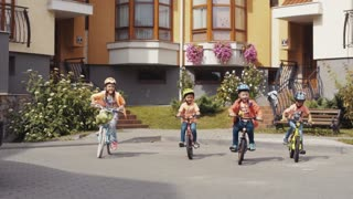 Four little children bikers in helmets, with backpacks cheerfully ride on their bikes towards the camera. Modern cottages on the background. Happy childhood, funny games, having fun
