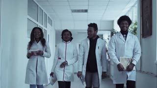 Four medical students walking down hospital corridor