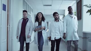 Four multiethnic medical university students in white coats walking in corridor, holding copybooks and smiling. Front view