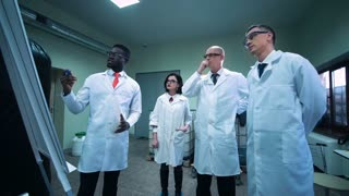 Four scientists in white lab coats standing indoors and discussing project that black man showing on white board