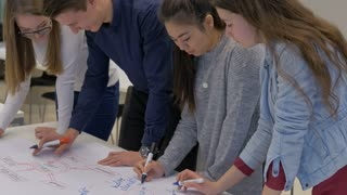 Friendly smart teenagers making a diagram on a big sheet of paper. Creative high school students working in a team collaborating on a project together. Classroom activity.