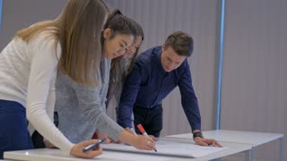 Friendly smart teenagers making a diagram on a big sheet of paper. High school students working in a team collaborating on a project together. Classroom activity.
