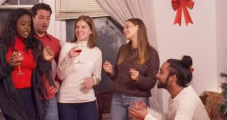 Friends dance and sing Christmas carols at a holiday party