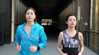 Asian women fitness friends running together in city