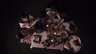 From above group of men and women sitting and dining at night together
