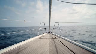 Front view on luxury sailing yacht boat nose with wooden parquet floor, swaying in open sea at sunny day. Relaxing and peaceful background holiday shot