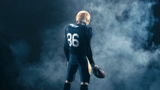 Full portrait rear view of Caucasian male American football standing with a ball, smoke background. 4K UHD RAW edited footage