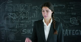 Futuristic portrait of a beautiful business girl (student) making a selection of Strategy in the background of a black board Concept ideas university college question choice of profession think future