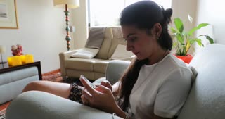 Girl Browses The Net On Her Smartphone Young Woman Seated In Living Room Sofa Checking Her Cellphone Browsing The Internet In 4 K