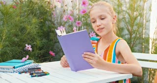 Girl Closing The Book At The Table Outdoors