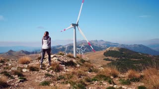 Girl looking at the field with windmills. Woman in mountains looking on the windmills