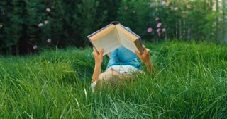 Girl Reading Book On The Green Grass Dolly Shot