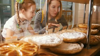 Girl with a pigtail and her mom look at the pies in the window choosing