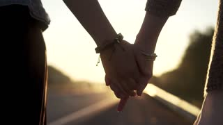girlfriends hand at sunset, closeup. girls hold hands and walk down the road. slow motion