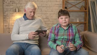 Grandfather and grandson are sitting on the couch. An old man uses a tablet, a young fat guy plays on the console game, loses. Video games. Home comfort, family idyll, cosiness concept, difference of