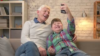 Grandfather and grandson are sitting on the sofa using a smartphone, making selfie. Rejoice in victory, laugh, they are happy. Young fat child and grandfather. 60 fps