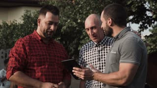 Group of adult and mature men standing with digital tablet in garden