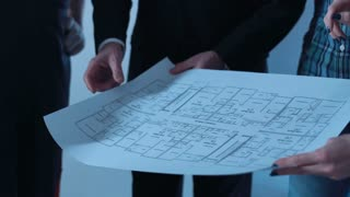 Group of designers and architects and workers discuss blueprint of future interior of room