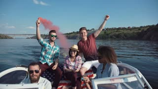 Group of diverse excited people sailing on boat playing with colored smoke bombs and celebrating Independence day