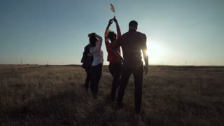 Group of five people warming against wind farm at sunset movement stabilized shot