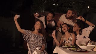 Group of friends taking selfie with smartphone together while sitting and dining
