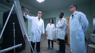 Group of multicultural scientists standing next to whiteboard and listening to the colleague showing them her research project