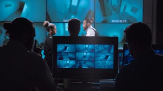 Group of professionals watching computer screen while working in office of video surveillance