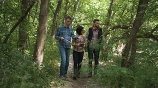 Group of three casual biologists walking in woods discussing problems of ecology