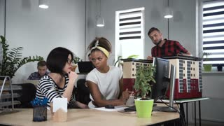 Group of three designers discussing architectural complex while working in office