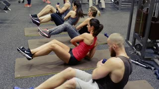 Group of young people in crossfit gym exercising their abdominal muscles, doing side crunches with dumbbells with elevated legs.