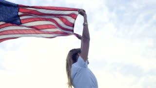 Hand held shot with soft focus of beautiful young model in hipster millennial outfit white skirt and trendy t shirt, holding american flag up in wind, proud of her nationality and homeland