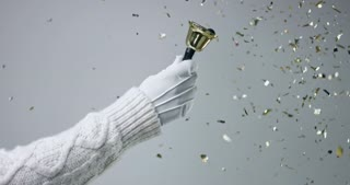 Hand in white leather glove and white cable sweater ringing a golden bell on white background