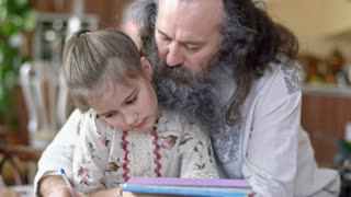 Handheld shot of little girl sitting on laps of senior man with grey bushy beard dressed in linen clothing with Slavic ornament and doing her homework as he helping her and explaining something