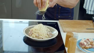 Handheld shot of unrecognizable male cook grating cheese on top of pasta with bacon, then showing plate to camera