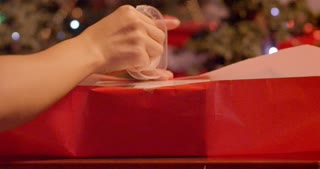 Hands wrapping and taping a present in front of Christmas decorations