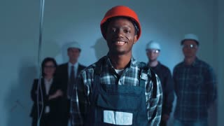 Handsome african young builder in protective form with hard hat standing and looking at camera on the construction site holding arms crossed at night in unfinished room opposite four people of builder