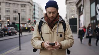 Handsome male walking the street and using his phone, in slow motion