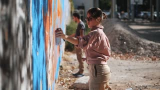 Handsome Talented Young Boy and girl making a colorful graffiti with aerosol spray on urban street wall. Cinematic toned slow motion footage. Creative art. Side view