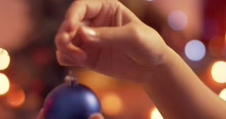 Woman hanging a blue ornament on the Christmas tree with glowing lights - slow motion