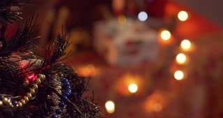 Woman hanging a red ball ornament on a Christmas tree with glowing lights - slow motion