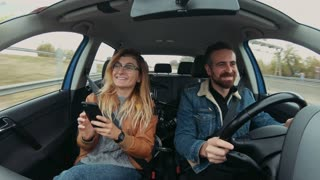 Happy and excited smiling just married couple, drive car during vacation or holiday road trip, smie and point out of window at tourist attractions, use smartphone to navigate