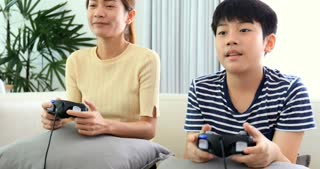 Happy asian family play game with smile face at home. Thai sister and brother playing game together .