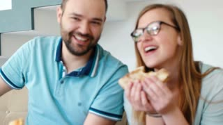 Happy Couple Eating Pizza At Home. Slow motion