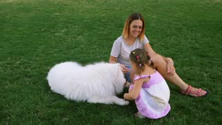 Happy people, family life, lifestyle, leisure, nature, animals, dogs, outdoors summer recreation. Portrait of mother and daughter smiling, sitting with big fluffy Samoyed on grass. slow motion
